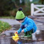 Ребенок в луже в резиновых сапожках